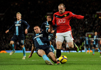 MANCHESTER, ENGLAND - FEBRUARY 23:  Wayne Rooney (R) of Manchester United is tackled by Matthew Upson of West Ham during the Barclays Premier League match between Manchester United and West Ham United at Old Trafford on February 23, 2010 in Manchester, En