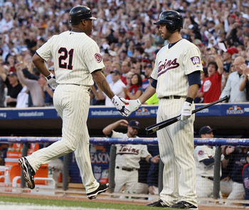MINNEAPOLIS - OCTOBER 07:  Delmon Young #21 of the Minnesota Twins is congratulated by teammate Jason Kubel #16 after Young scored a run against the New York Yankees during game two of the ALDS on October 7, 2010 at Target Field in Minneapolis, Minnesota.