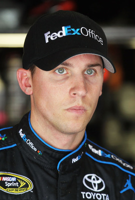 FONTANA, CA - MARCH 26:  Denny Hamlin, driver of the #11 FedEx Toyota, stands in the garage area during practice for the NASCAR Sprint Cup Series Auto Club 400 at Auto Club Speedway on March 26, 2011 in Fontana, California.  (Photo by Jeff Gross/Getty Ima