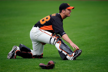 SCOTTSDALE, AZ - MARCH 14:  Buster Posey #28 of the San Francisco Giants stretches before playing against the Milwaukee Brewers during the spring training baseball game at Scottsdale Stadium on March 14, 2011 in Scottsdale, Arizona.  (Photo by Kevork Djan