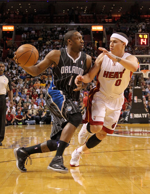 MIAMI, FL - MARCH 03: Gilbert Arenas #1 of the Orlando Magic drives against Mike Bibby #0 of the Miami Heat during a game at American Airlines Arena on March 3, 2011 in Miami, Florida. NOTE TO USER: User expressly acknowledges and agrees that, by download