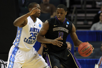 CHARLOTTE, NC - MARCH 20:  Matthew Bryan-Amaning #11 of the Washington Huskies moves the ball against Justin Knox #25 of the North Carolina Tar Heels during the third round of the 2011 NCAA men's basketball tournament at Time Warner Cable Arena on March 2