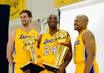 EL SEGUNDO, CA - SEPTEMBER 25:  Kobe Bryant #24  of the Los Angeles Lakers smiles as he holds two NBA Finals Larry O'Brien Championship Trophy's as he poses for a photograph with teammates Pau Gasol #16 and Derek Fisher #2 during Media Day at the Toyota C