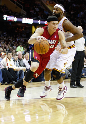 CLEVELAND - MARCH 29: Mike Bibby #0 of the Miami Heat drives to the basket in front of Baron Davis #85 of the Cleveland Cavaliers during the game against on March 29, 2011 at Quicken Loans Arena in Cleveland, Ohio. NOTE TO USER: User expressly acknowledge