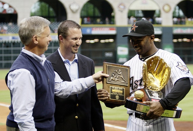 HOUSTON - APRIL 09:  Michael Bourn of the Houston Astos receives from Houston Astros general manager Ed Wade, left,  his Lou Brock Award for most stolen bases in the National League and from Shandy Adelman, center, of Rawlings presented Bourn his gold glo