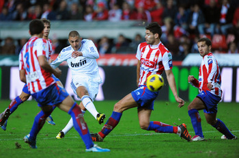 GIJON, SPAIN - NOVEMBER 14: Karim Benzema of Real Madrid shoots through he Sporting Gijon defense during the La Liga match between Sporting Gijon and Real Madrid at El Molinon Stadium on November 14, 2010 in Gijon, Spain.  (Photo by Denis Doyle/Getty Imag