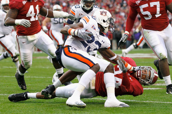 TUSCALOOSA, AL - NOVEMBER 26:  Onterio McCalebb #23 of the Auburn Tigers is wrestled to the ground by DeQuan Menzie #24 of the Alabama Crimson Tide at Bryant-Denny Stadium on November 26, 2010 in Tuscaloosa, Alabama.  (Photo by Kevin C. Cox/Getty Images)