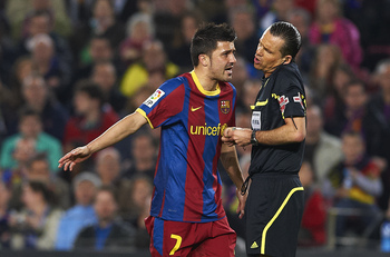 BARCELONA, SPAIN - MARCH 19:  David Villa of Barcelona speaks with referee Cesar Mu?iz Fernandez during the La Liga match between Barcelona and Getafe at Camp Nou on March 19, 2011 in Barcelona, Spain. Barcelona won 2-1.  (Photo by Manuel Queimadelos Alon