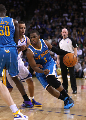 OAKLAND, CA - JANUARY 26:  Chris Paul #3 of the New Orleans Hornets dribbles around a pick while defended by Stephen Curry #30 of the Golden State Warriors at Oracle Arena on January 26, 2011 in Oakland, California.  NOTE TO USER: User expressly acknowled