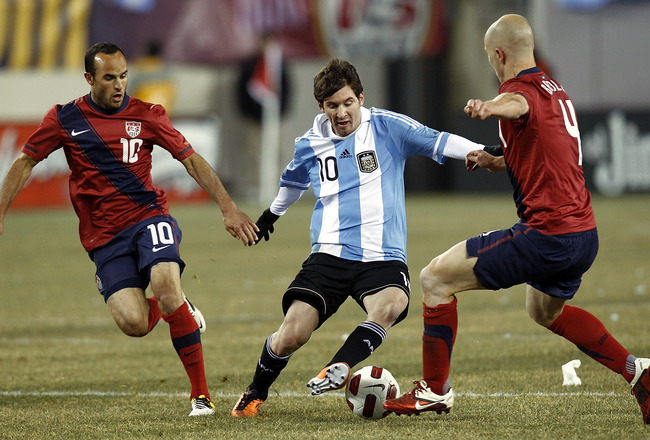 EAST RUTHERFORD, NJ - MARCH 26:  Lionel Messi #10 of Argentina dribbles between Landon Donovan #10 and Michael Bradley #4 of the United States during the first half of a friendly match at New Meadowlands Stadium on March 26, 2011 in East Rutherford, New J