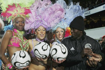 LONDON - FEBRUARY 28:  Dwight Yorke of Trinidad and Tobago meets the half time dancing girls during the International Friendly between Trinidad and Tobago and Iceland at Loftus Road on February 28, 2006 in London, England. (Photo by Bryn Lennon/Getty Imag