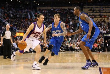 PHOENIX - DECEMBER 11:  Steve Nash #13 of the Phoenix Suns handles the ball under pessure from Jason Williams #44 of the Orlando Magic during the NBA game at US Airways Center on December 11, 2009 in Phoenix, Arizona. The Suns defeated the Magic 106-103.