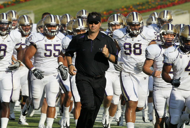 LOS ANGELES - OCTOBER 2:   Head coach Steve Sarkisian of the Washington Huskies runs off the field with his team after warmups for th game with the USC Trojans at the Los Angeles Memorial Coliseum on October 2, 2010 in Los Angeles, California.    (Photo b