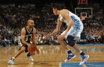 DENVER, CO - MARCH 23:  Tony Parker #9 of the San Antonio Spurs dribbles the ball against Danilo Gallinari the Denver Nuggets at the Pepsi Center on March 23, 2011 in Denver, Colorado. The Nuggets defeated the Spurs 115-112. NOTE TO USER: User expressly a