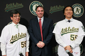 OAKLAND, CA - DECEMBER 14:  Hideki Matsui (R) stands with Oakland Athletics general manager Billy Beane (C) and San Francisco Consul General Hiroshi Inomata (L) pose for a photograph during a press conference where he was introduced as the newest member o