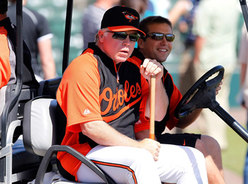SARASOTA, FL - MARCH 03:  Manager Buck Showalter #26 of the Baltimore Orioles gets a ride back to the clubhouse just before the start of the Grapefruit League Spring Training Game against the Minnesota Twins at Ed Smith Stadium on March 3, 2011 in Sarasot