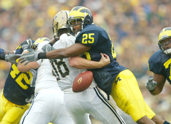 ANN ARBOR, MI - OCTOBER 25:  Ernest Shazor #25 of the Michigan Wolverines hits quarterback Kyle Orton #18 of the Purdue Boilermakers and causes a fumble on October 25, 2003 at Michigan Stadium in Ann Arbor, Michigan. Purdue recovered the fumble.  (Photo b