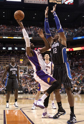 PHOENIX, AZ - MARCH 13:  Hakim Warrick #21 of the Phoenix Suns attempts a shot over Dwight Howard  #12 of the Orlando Magic during the NBA game at US Airways Center on March 13, 2011 in Phoenix, Arizona. The Magic defeated the Suns 111-88.  NOTE TO USER: