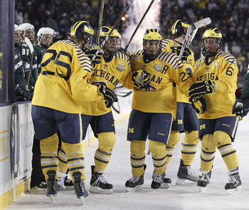 ANN ARBOR, MI - DECEMBER 11:  David Wohlberg #25 of the Michigan Wolverines celebrates a third period goal with and Lee Moffie #13, Louie Caporusso #29 and Brandon Burlon #6 while playing the Michigan State Spartans at Michigan Stadium on December 11, 201