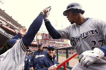 CINCINNATI, OH - MARCH 31: Carlos Gomez #27 of the Milwaukee Brewers celebrates with teammates after a first inning home run during the opening day game against the Cincinnati Reds at Great American Ballpark on March 31, 2011 in Cincinnati, Ohio. (Photo b