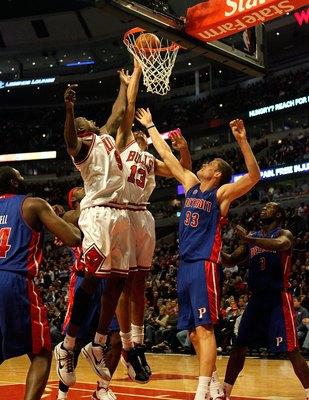 CHICAGO - DECEMBER 02: Loul Deng #9 and Joakim Noah #13 of the Chicago Bulls jump for a rebound over Jonas Jerebko #33 of the Detroit Pistons at the United Center on December 2, 2009 in Chicago, Illinois. The Bulls defeated the Pistons 92-85. NOTE TO USER