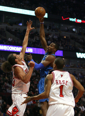 CHICAGO - FEBRUARY 24:  Dwight Howard #12 of the Orlando Magic attempts a shot aganst Joakim Noah #13 and Derrick Rose #1 of the Chicago Bulls at the United Center on Feberuary 24, 2009 in Chicago, Illinois.  NOTE TO USER: User expressly acknowledges and