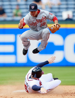 ATLANTA - SEPTEMBER 15:  Danny Espinosa #18 of the Washington Nationals turns a double play as he leaps over Freddie Freeman #5 of the Atlanta Braves at Turner Field on September 15, 2010 in Atlanta, Georgia.  (Photo by Kevin C. Cox/Getty Images)