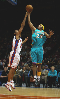 NEW YORK - JANUARY 11:  J.R. Smith #23 of the New Orleans Hornets puts up a shot against Allan Houston #20 of the New York Knicks on January 11, 2005 at Madison Square Garden in New York City. (Photo by Ezra Shaw/Getty Images)
