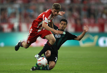 MUNICH, GERMANY - AUGUST 20:  Thomas Mueller of Bayern is tackled by Josue of Wolfsburg during the Bundesliga match between FC Bayern Muenchen and VfL Wolfsburg at Allianz Arena on August 20, 2010 in Munich, Germany.  (Photo by Clive Brunskill/Getty Image