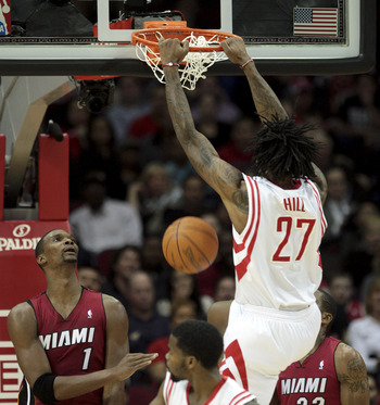 HOUSTON - DECEMBER 29:  Jordan Hill #27 of the Houston Rockets dunks over Chris  Bosh #1 of the Miami Heat in the first half at Toyota Center on December 29, 2010 in Houston, Texas.  NOTE TO USER: User expressly acknowledges and agrees that, by downloadin