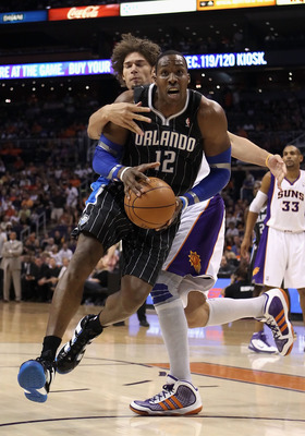 PHOENIX, AZ - MARCH 13:  Dwight Howard #12 of the Orlando Magic drives to the basket during the NBA game against the Phoenix Suns at US Airways Center on March 13, 2011 in Phoenix, Arizona. The Magic defeated the Suns 111-88. NOTE TO USER: User expressly