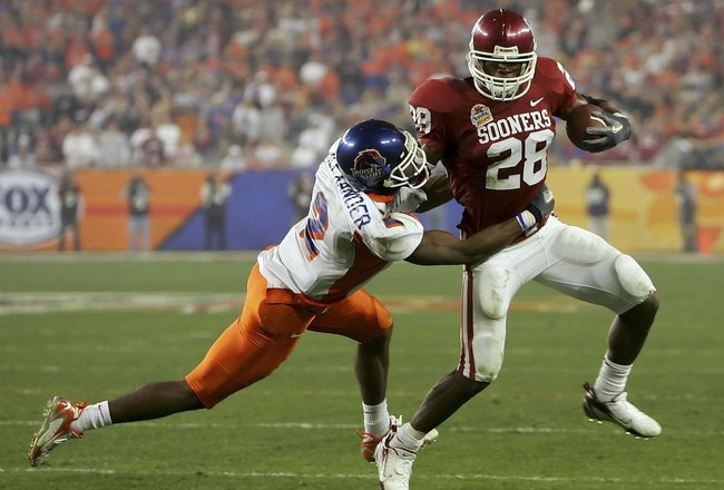 GLENDALE, AZ - JANUARY 1:  Adrian Peterson #28 of the Oklahoma Sooners looks to break a safety Gerald Alexander #2 of the Boise State Broncos tackle in the first half at the Tostito's Fiesta Bowl against the Boise State Broncos at University of Phoenix St