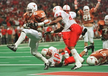 7 Dec 1996:  Running Back Priest Holmes #33 of the University of Texas Longhorns high steps into the end-zone past Ralph Brown #22 and Mike Minter #10 of the University of Nebraska Cornhuskers for the Longhorns first touchdown during the inaugural Big 12