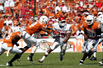 DALLAS - OCTOBER 17:  Running back Chris Brown #29 of the Oklahoma Sooners runs the ball past Aaron Williams #4 of the Texas Longhorns at Cotton Bowl on October 17, 2009 in Dallas, Texas.  (Photo by Ronald Martinez/Getty Images)