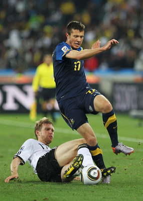 DURBAN, SOUTH AFRICA - JUNE 13:  Per Mertesacker of Germany tackles Nikita Rukavytsya of Australia during the 2010 FIFA World Cup South Africa Group D match between Germany and Australia at Durban Stadium on June 13, 2010 in Durban, South Africa.  (Photo
