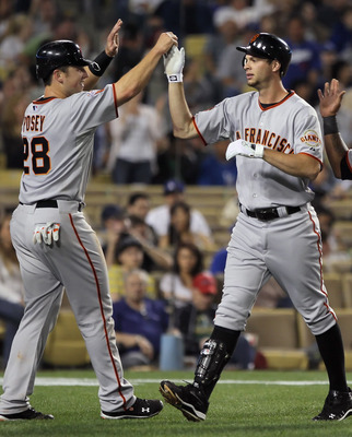 LOS ANGELES, CA - APRIL 01:  Brandon Belt (center) #9 of the San Francisco Giants is congratulated by Buster Posey (L) #28 and Pablo Sandoval (R) #48 after hitting a three-run homerun against the Los Angeles Dodgers in the fourth inning at Dodger Stadium