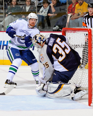NASHVILLE, TN - MARCH 29:  Daniel Sedin #22 of the Vancouver Canucks fires a shot off the post next to Pekka Rinne #35 of the Nashville Predators on March 29, 2011 at the Bridgestone Arena in Nashville, Tennessee.  (Photo by Frederick Breedon/Getty Images