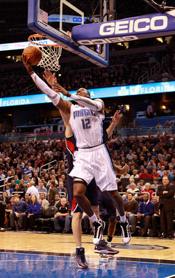 ORLANDO, FL - DECEMBER 06:  Dwight Howard #12 of the Orlando Magic attempts a shot against  Zaza Pachulia #27 of the Atlanta Hawks during the game at Amway Arena on December 6, 2010 in Orlando, Florida. NOTE TO USER: User expressly acknowledges and agrees