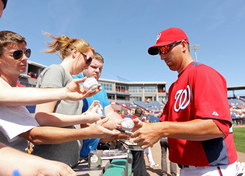 VIERA, FL - MARCH 02:  Adam LaRoche #25 of the Washington Nationals signs autographs during a Spring Training game against the Florida Marlins at Space Coast Stadium on March 2, 2011 in Viera, Florida.  (Photo by Mike Ehrmann/Getty Images)