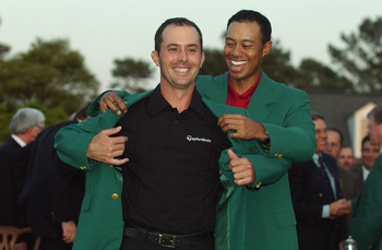 AUGUSTA, GA - APRIL 13:  Mike Weir of Canada is presented with the green jacket by Tiger Woods of the USA after winning the play off after the final round of the 2003 Masters Tournament at the Augusta National Golf Club in Augusta, Georgia on April 13, 20