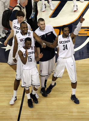 HOUSTON, TX - APRIL 02:  Kemba Walker #15, Charles Okwandu #35 and Alex Oriakhi #34 of the Connecticut Huskies celebrate after defeating the Kentucky Wildcats during the National Semifinal game of the 2011 NCAA Division I Men's Basketball Championship at
