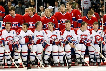 MONTREAL- DECEMBER 4:  Former Montreal Canadiens (Front Row L-R) Patrice Brisebois, Eric Desjardins, Lyle Odelein, Guy Carbonneau, Stephane Richer, Claude Lemieux and Vincent Damphousse sir in front of current Montreal Canadiens (Back Row L-R) Sergei Kost