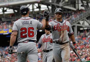 WASHINGTON, DC - APRIL 03: Martin Prado #14 of the Atlanta Braves (R) is congratulated by teammate Dan Uggla #26 after scoring against the Washington Nationals during the seventh inning at Nationals Park on April 3, 2011 in Washington, DC.  (Photo by Rob