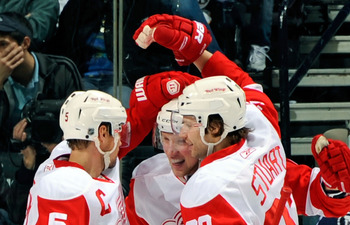 NASHVILLE, TN - APRIL 02:  Nicklas Lidstrom #5 and Brad Stuart #23 of the Detroit Red Wings congratulate Jonathan Ericsson #52 on scoring a goal against the Nashville Predators on April 2, 2011 at the Bridgestone Arena in Nashville, Tennessee.  (Photo by