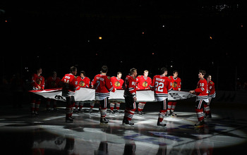 CHICAGO - OCTOBER 09: Members of the Chicago Blackhawks carry the Stanley Cup Championship banner across the ice in a ceremony before the Blackhawks season home opening game against the Detroit Red Wings at the United Center on October 9, 2010 in Chicago,