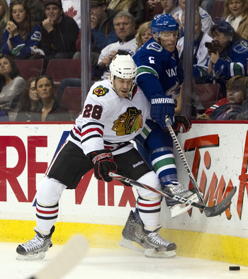 VANCOUVER, CANADA - FEBRUARY 4: Jake Dowell #28 of the Chicago Blackhawks pins Christian Ehrhoff #5 of the Vancouver Canucks up against the end boards during the first period in NHL action on February 04, 2011 at Rogers Arena in Vancouver, British Columbi