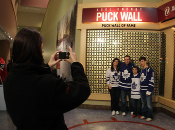 ST PAUL, MN - MARCH 22: Fans pose in front of the puck wall of fame prior to the game between the Minnesota Wild and the Toronto Maple Leafs at the Xcel Energy Center on March 22, 2011 in St Paul, Minnesota. (Photo by Bruce Bennett/Getty Images)