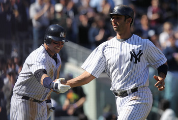 NEW YORK, NY - APRIL 03:  Jorge Posada #20 of the New York Yankees celebrates his second homerun with scoring runner Nick Swisher #33 against the Detroit Tigers at Yankee Stadium on April 3, 2011 in the Bronx borough of New York City.  (Photo by Nick Laha