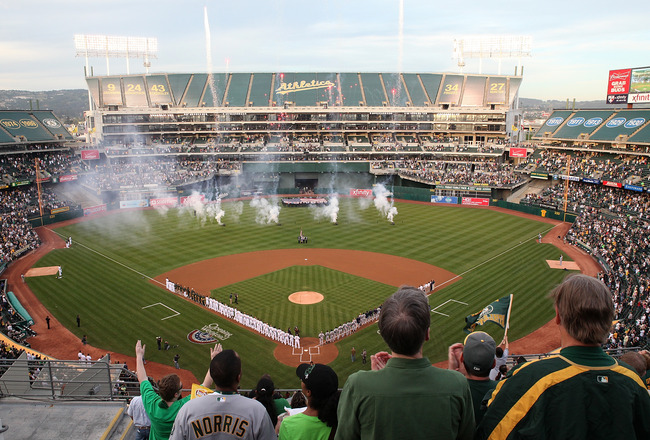 OAKLAND, CA - APRIL 01:  Fans watch the singing of the National Anthem before the start of the Opening Day game with the Oakland Athletics and the Seattle Mariners at the Oakland-Alameda County Coliseum on April 1, 2011 in Oakland, California  (Photo by J