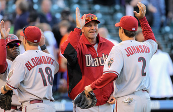 DENVER, CO - APRIL 01:  Kelly Johnson #2 of the Arizona Diamondbacks is welcomed off the field by manager Kirk Gibson #23 and Willie Bloomquist #18 of the Arizona Diamondbacks is welcomed off the field by Eric Young  of the Arizona Diamondbacks as they ce